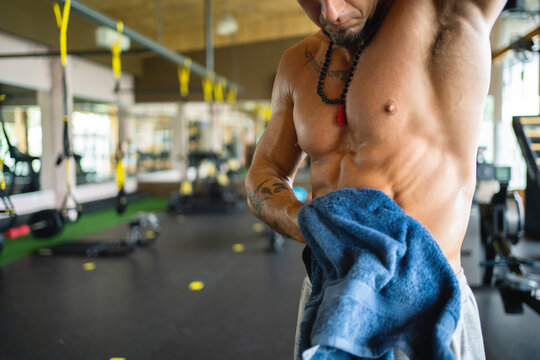 Cropped unrecognizable muscular male athlete wiping sweat from torso with towel after active workout in gym