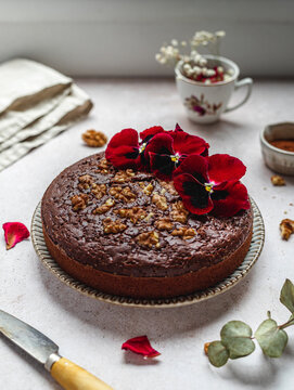 From above of sweet chocolate cake garnished with red flowers and walnuts served on table