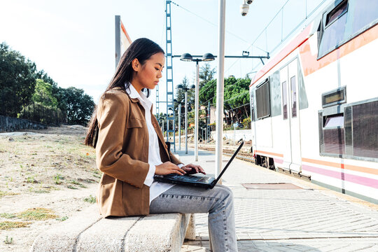 Side view of focused Asian female in mask sitting on bench at railway station and browsing laptop while waiting for train