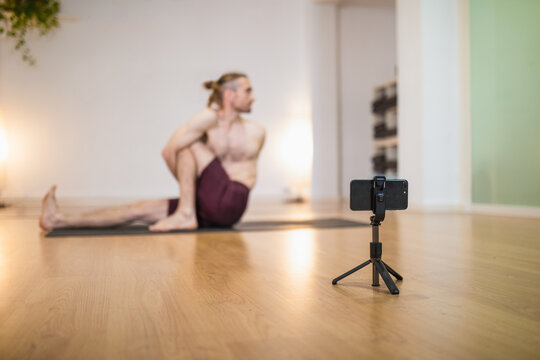 Soft focus of smartphone on tripod recording yoga session of coach practicing Marichyasana on sports mat in studio