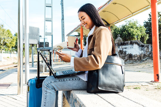 Side view of happy Asian female freelancer sitting on bench with laptop and takeaway coffee and browsing smartphone while waiting for train at railway station and working remotely