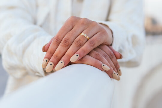 Crop unrecognizable bride with manicured nails and in golden wedding ring leaning on white railing
