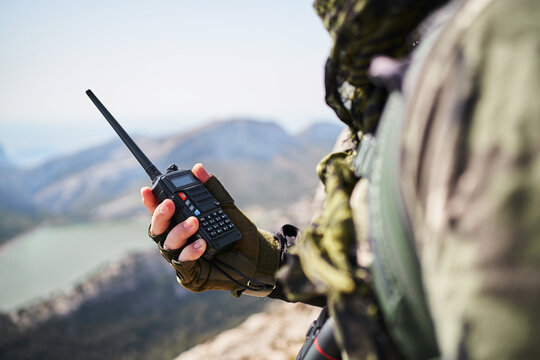Side view of crop bearded soldier in uniform speaking on walkie talkie standing on mountain on sunny day
