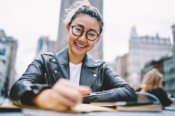 Obraz Portrait of happy Chinese tourist sitting in street cafe and smiling at camera enjoying leisure time on vacations, cheerful Japanese hipster girl in trendy spectacles for provide eyes correction - fototapety do salonu