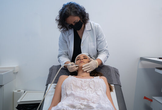 Professional cosmetologist using special equipment and doing microdermabrasion facial treatment for female client in modern beauty clinic