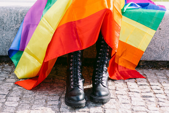 Crop unrecognizable person in black brutal boots and with rainbow LGBT flag on city street
