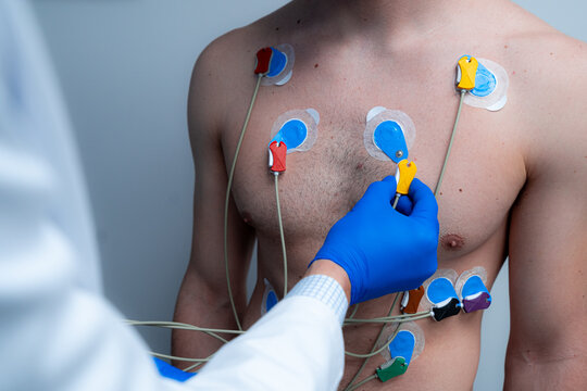 Crop anonymous medic connecting electrodes to chest of male patient for conducting ECG diagnostic of heart