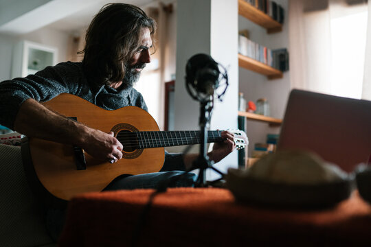 Middle aged ethnic male guitarist tuning acoustic guitar against laptop and microphone in house room