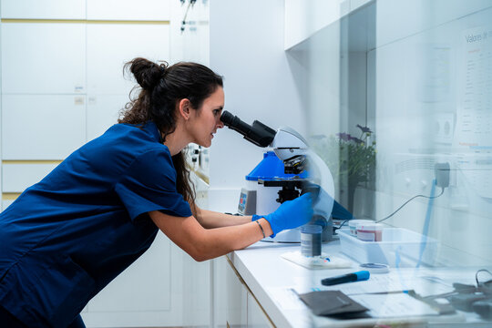 Side view of female vet in blue uniform looking through microscope while working in lab