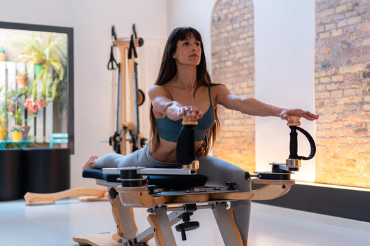 Concentrated fit female stretching legs and doing lunge exercises on pilates reformer during training in gym