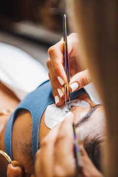 Crop unrecognizable cosmetologist with tweezers applying fake eyelashes for extension on eye of ethnic client with face protective mask in salon during coronavirus pandemic