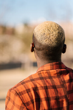 Back view of unrecognizable African American male in tartan outfit standing in town