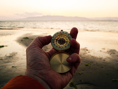 POV crop anonymous adventurer checking route with retro compass while standing on sandy beach near sea at sunset