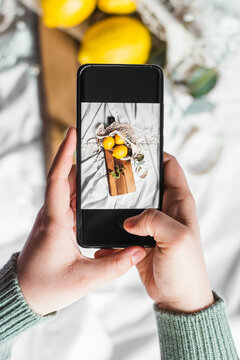 Top view of crop unrecognizable person touching screen of cellphone while taking photo of lemons on cutting board