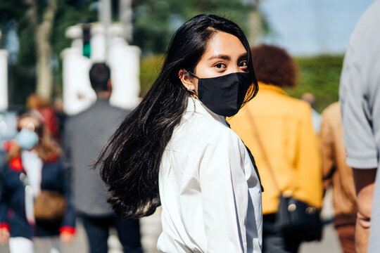 Back view of Asian female with flying hair wearing protective mask walking in crowd and looking at camera