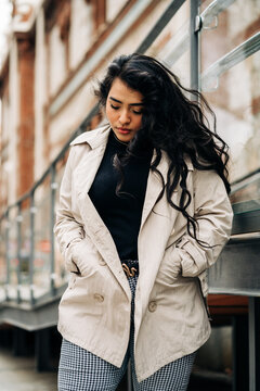 Low angle of plus size female wearing trendy coat standing with hands in pockets against city street and looking down