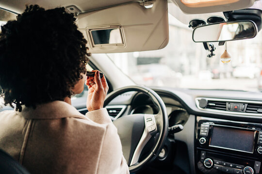 Back view of unrecognizable African American female driver sitting in automobile and applying lipstick while looking at mirror