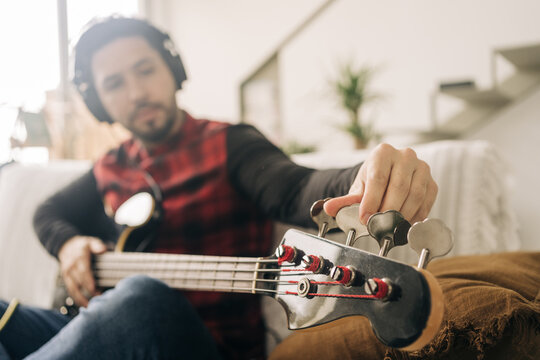 Bearded male musician in headset tuning bass guitar while sitting on couch in living room