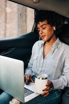 Young content cheerful African American female working with netbook and having mug of coffee to go riding on backseat in car