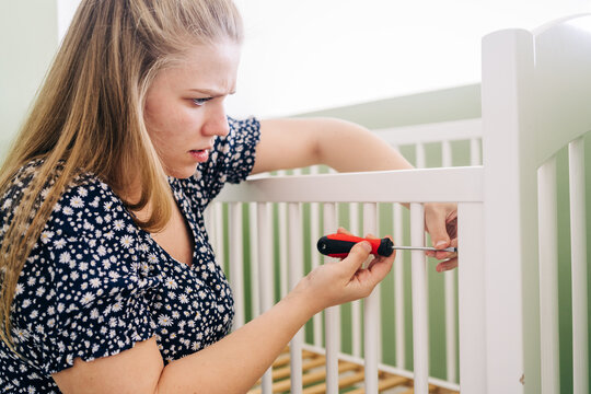 Side view woman with screwdriver leaning forward while mounting crib at home on sunny day
