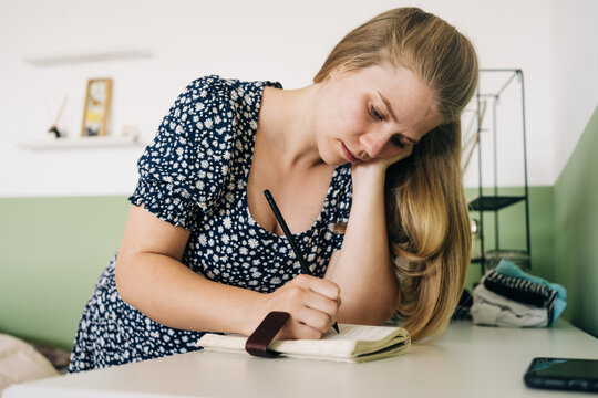 Young female leaning with hand on desk while taking notes in notepad at home in daylight