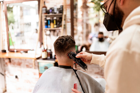 Male hairstylist in eyeglasses making haircut to adult client in hairdressing salon during COVID 19 pandemic