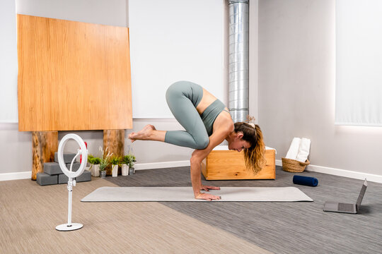 Full length of fit young woman performing Bakasana while practicing yoga on man in modern apartment near smartphone on tripod