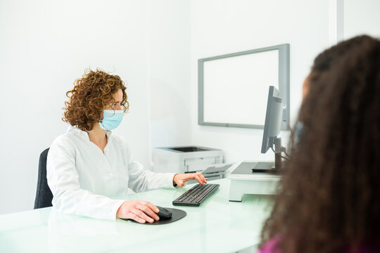 Cropped unrecognizable African American woman during appointment sitting at female doctor in face mask with office desk protected by a perspex glass screen at modern clinic during coronavirus outbreak