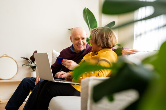 Cheerful mature couple making payment with plastic card during online shopping via laptop at home