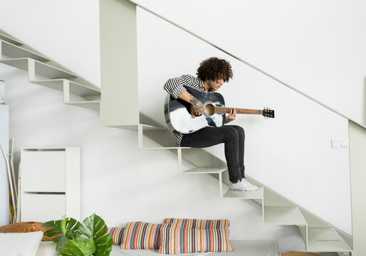 Side view of young hipster male musician playing acoustic guitar while sitting on staircase and looking down in flat