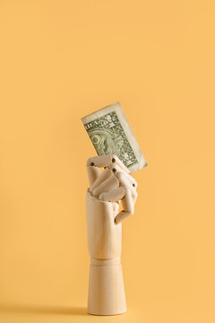 Dollar banknote in wooden hand placed on orange background in studio showing financial concept