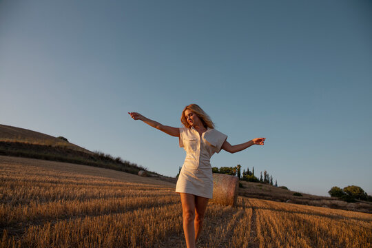 Peaceful female in elegant dress standing on dry field in rural area and looking down