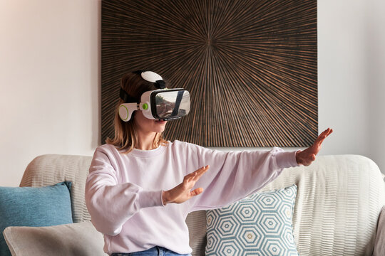 Content young female in casual outfit watching video using VR goggles while sitting on comfortable sofa at home