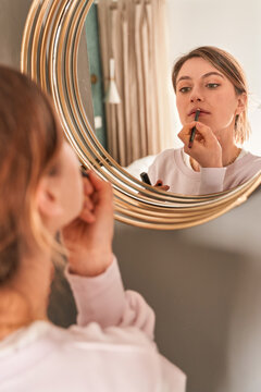 Crop young female with blond hair in casual clothes looking in mirror and applying lip liners in sunny morning