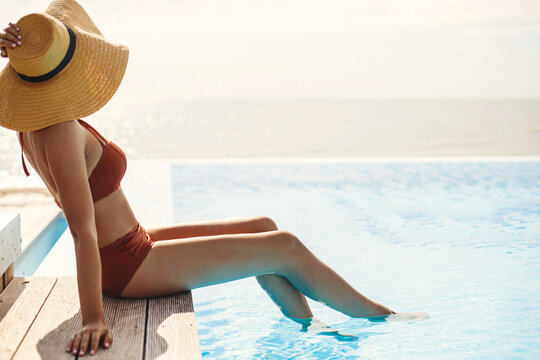 Beautiful woman in hat tanning on wooden pier at blue pool edge, enjoying summer vacation. Slim young female relaxing at tropical resort and sunbathing at swimming pool. Travel and Holidays