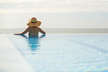 Obraz Beautiful woman in hat relaxing at edge in blue pool, enjoying summer vacation and calm sea view. Slim young female relaxing at tropical resort in swimming pool. Travel and Holidays. Space for text - fototapety do salonu