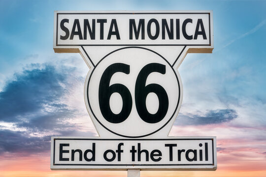 Low angle of signboard with inscription Santa Monica 66 End of the Trail on background of colorful sundown sky
