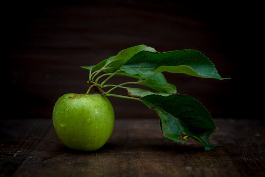 Whole ripe green apple with foliage and pure small aqua drips on black background