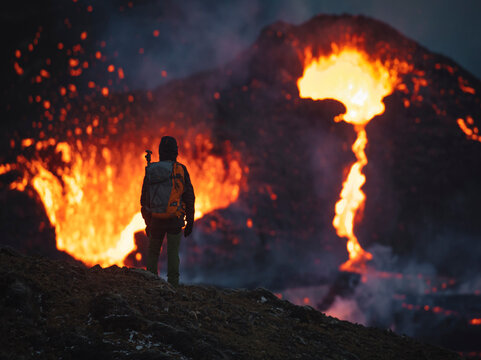 Man explorer observing the magma sparks out of the volcano Fagradalsfjall in Iceland between clouds of smoke