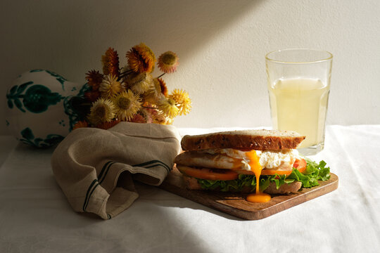 Appetizing homemade sandwich with poached eggs and fresh tomatoes and lettuce served with glass of juice for breakfast on table with flowers