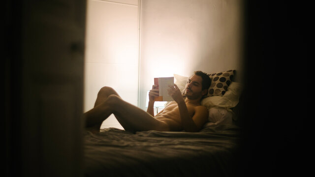 Nude male relaxing on comfortable bed and reading interesting book in bedroom in evening