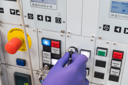Crop unrecognizable professional male laboratory assistant in white robe and latex gloves pressing buttons on modern equipment