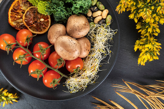 Top view of plate with bundle of fresh cherry tomatoes near cooked potatoes and sprouts on gray background with flowers