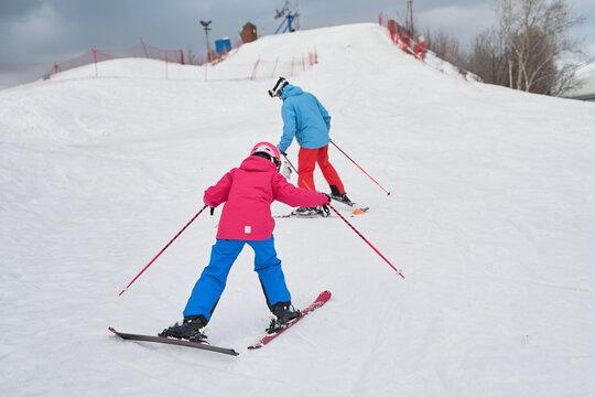 Full body faceless parent in warm sportswear and helmet teaching little kid to ski alongside snowy hill slope in winter ski resort