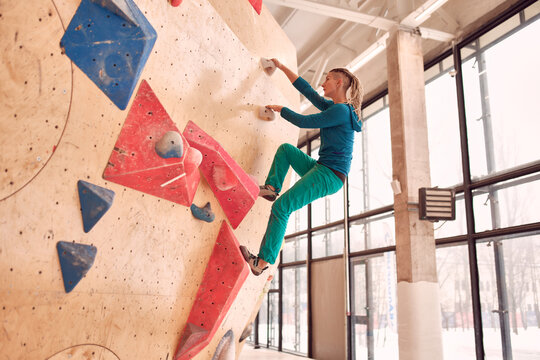 Female athlete climbing artificial wall during bouldering workout in professional gym