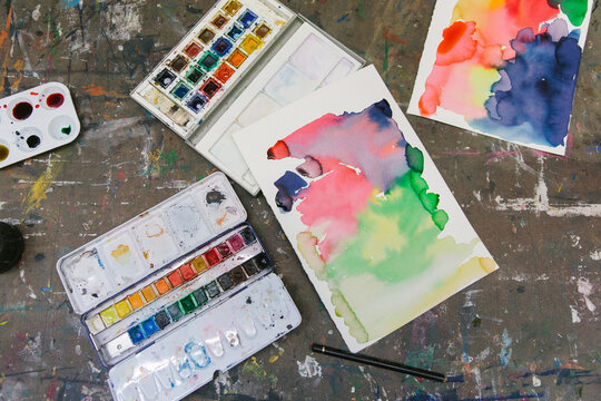 From above of watercolor paint palettes and abstract pictures arranged on table in creative studio