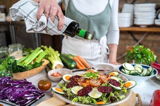 Crop unrecognizable female pouring olive oil from bottle on yummy vegetarian salad with assorted vegetables and sesame seeds at home