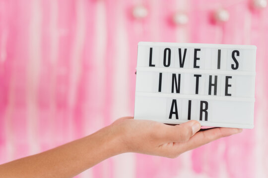 Hands holding a light box with Love is in the air message