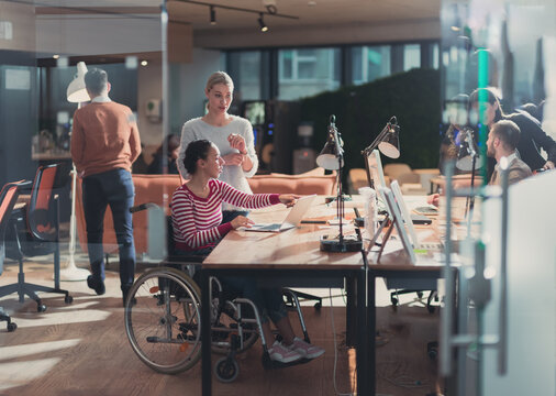 Disabled businesswoman in a wheelchair in modern coworking office space. Colleagues in background. Disability and handicap concept. Selective focus