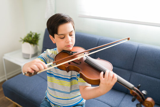 Little student practicing a song on the violin